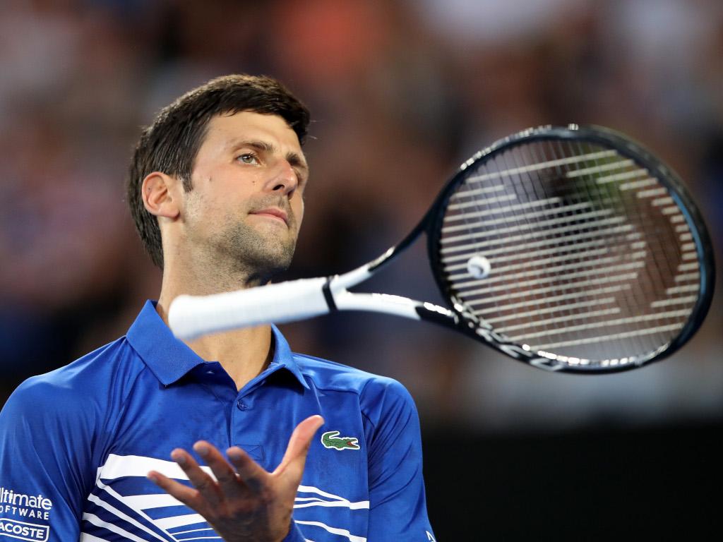 Novak Djokovic tosses his racket
