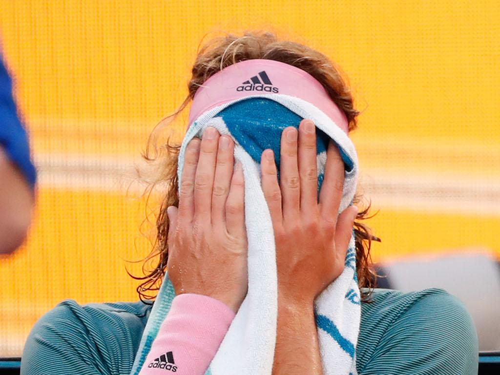 Stefanos Tsitsipas wipes his face