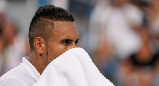 Nick Kyrgios wiping his face