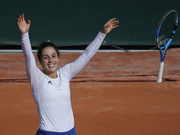 Martina Trevisan throws her racket in the air in celebration after upsetting Kiki Bertens