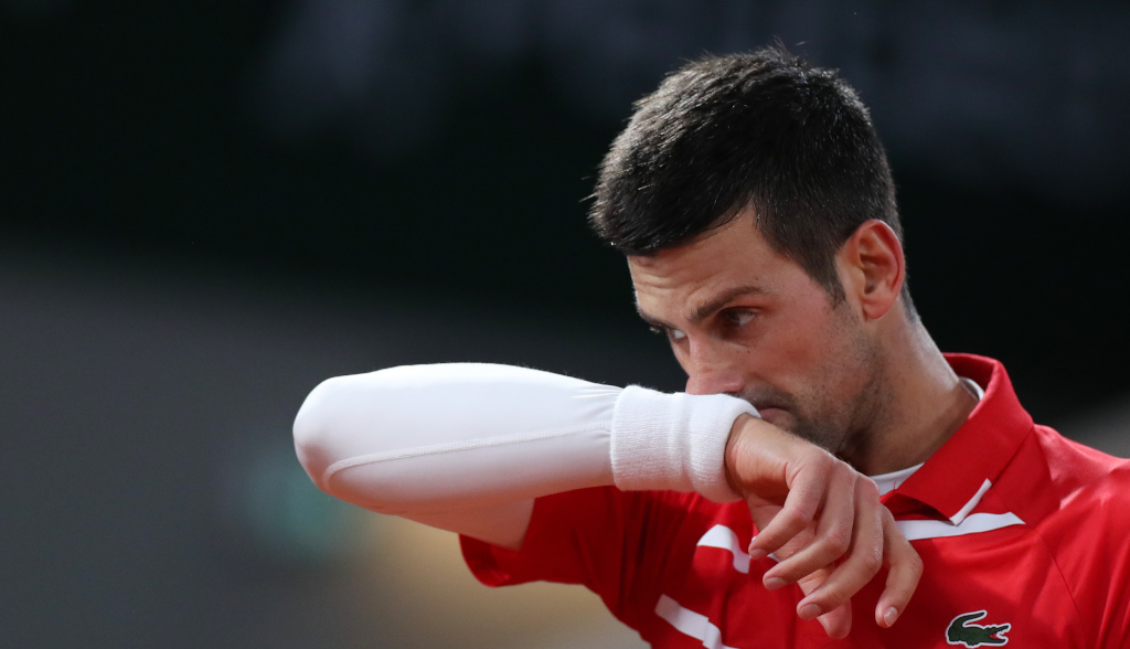 Novak Djokovic wiping his face