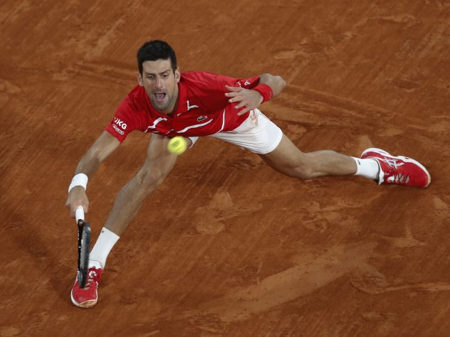 Novak Djokovic slides into a forehand