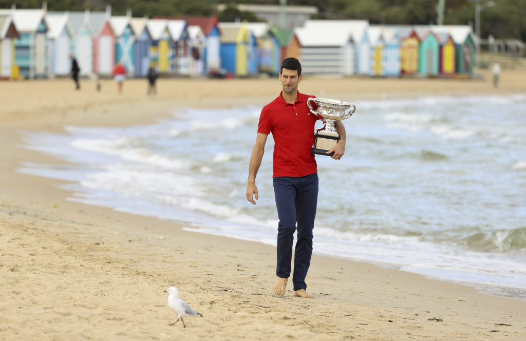 Novak Djokovic on the beach with Australian Open trophy