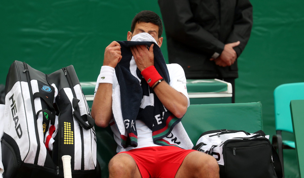 Novak Djokovic wipes his face