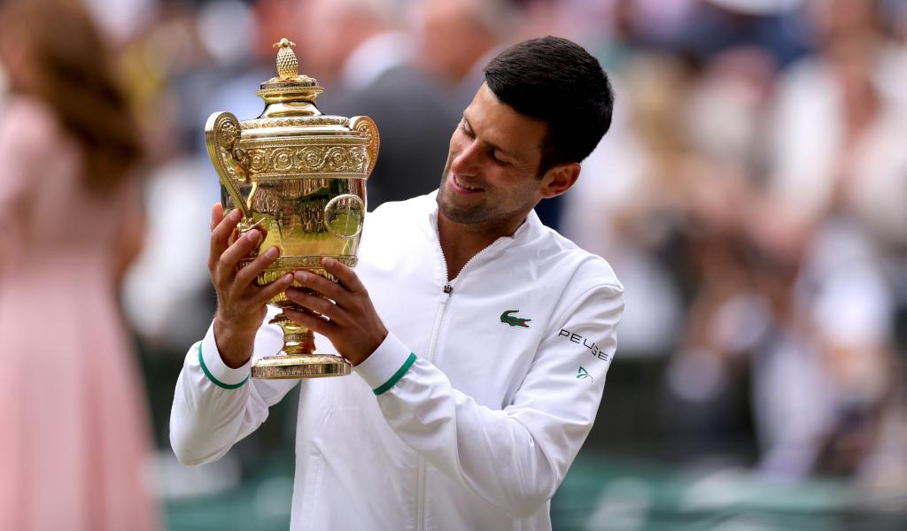 Novak Djokovic admires the Wimbledon trophy