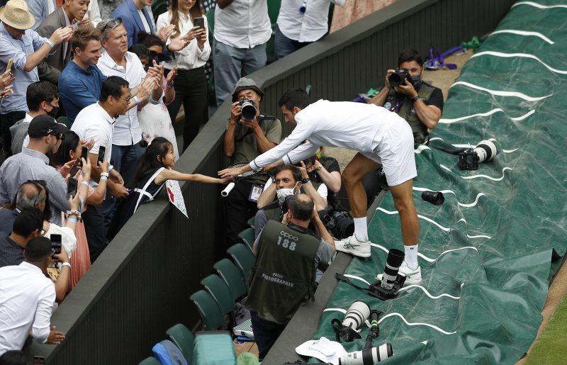 Novak Djokovic hands racket to girl