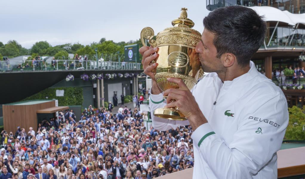 Novak Djokovic kisses the Wimbledon trophy