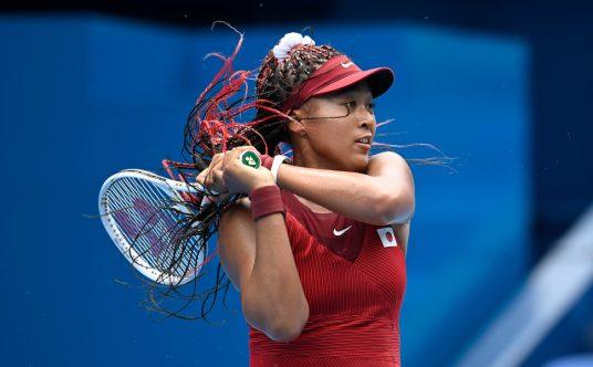 Naomi Osaka swinging at the Tokyo Olympics
