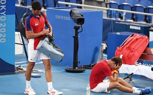 Novak Djokovic leaves tennis arena while Pablo Carreno Busta celebrates